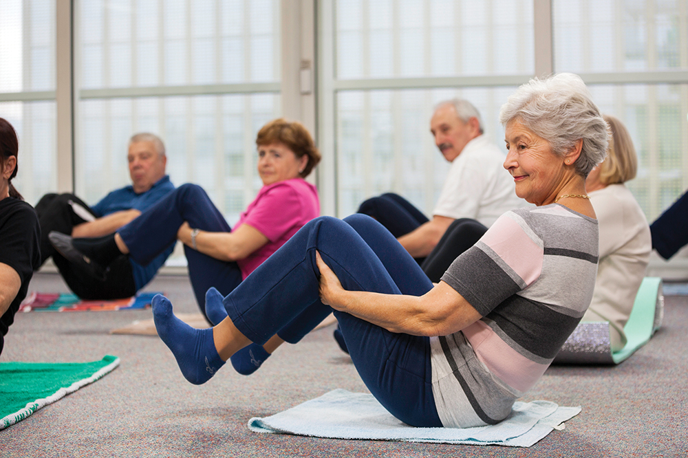 Group of senior adults sitting on the floor and doing stretching pilates exercises with raising their legs.