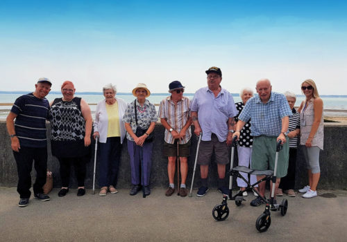 A group from Wheel House pose for a photo at the seaside