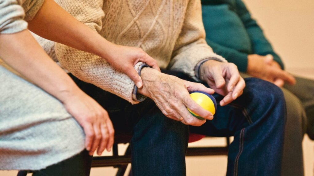 old person holding ball in hand