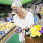 Elderly lady buying fruit at market