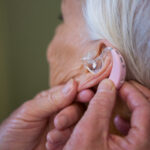 doctor inserting a hearing aid